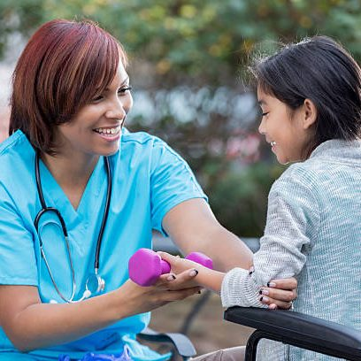 Mid adult African American female physical therapist or nurse works with a young female wheelchair-bound patient. The nurse is showing the girl proper form to lift a hand weight. The nurse is wearing scrubs and a stethoscope.